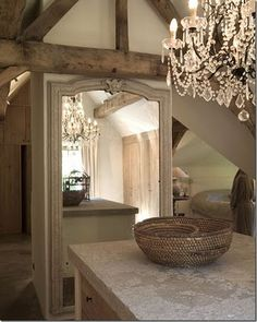 Use a crystal chandelier in the kitchen with reclaimed wood, as well as a large mirror to reflect it.