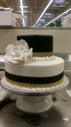 Custom 2 tier. Gold diamante, black fondant strip, large white Dahlia. White and black buttercream icing