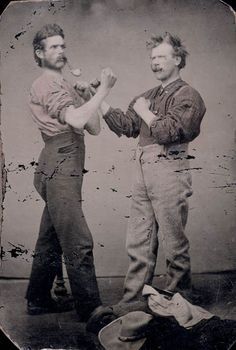 Two men with pipes posing as boxers / Deux hommes, pipes à la bouche, prenant une pose de boxeur. Library and Archives Canada via Flickr.