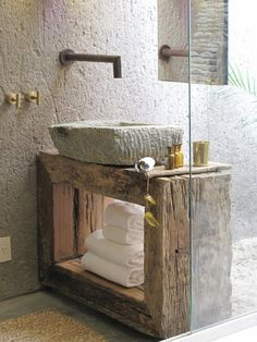 Rustic finishes like rough, thick-cut wood, carved stone sink basin, and textured wall combine to create an unusual but beautiful bath.