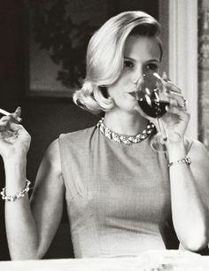 Betty Draper has a drink and a smoke.