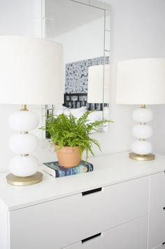 Modern white dresser with DIY blue legs and white and gold table lamps via Thou Swell @thouswellblog