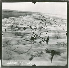 """May 6, 1944. Normandy Beach. German troops scatter as Lt. Albert Lanker flies fast and low over the beach in a F-5 Lightning """"Outlaw."""" Lanker's job was to photograph beach obstructions for use by planners of the D-Day invasion. It was only his third mission."""