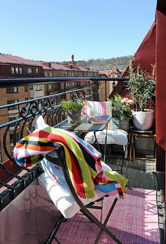 simply decorates small balcony with a few pots of plant and garden furniture... very nice!