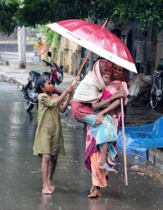 This is a woman carrying a man who is unable to walk as a child holds an umbrella to keep the rain off. It shows how humane people can be heartfelt-touching We Are The World, People Around The World, Old M, Amazing India, Parasols, Walking In The Rain, Under My Umbrella, Faith In Humanity, Rainy Days