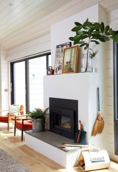 Shiplap walls, light hardwood floors, casual fireplace styling and bright red arm chairs for a pop of color.