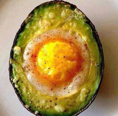 Scoop out the pit and a little more of the avocado. Crack an egg into the center. Sprinkle it with Cayenne pepper and cheese if you so desire. Bake in the oven at 180 degrees until egg is cooked to the level you like.