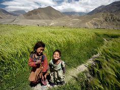Barley Fields, Mustang  Photograph by David Stubbs/Aurora Photos    Small girls traverse a barley field beneath barren mountain peaks in the windswept region of Mustang. Located north of the main Himalayan massif, Mustang is cut off from the Indian monsoon that waters much of Nepal. Snowmelt from mountain peaks and scant summer rains feed the region's carefully maintained system of irrigation channels.