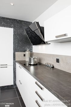 Une cuisine en métal noire et blanche. Pour la hotte