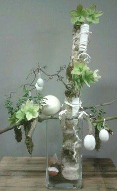 een mooi gevormde stok waterbuisjes met wol omkleed en een enkele bloem: