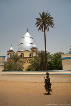 Sudan, Khartoum. A woman walks past the Mahdi's Tomb on a hot Khartoum day.