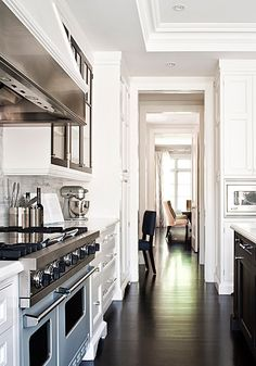 My idea of the perfect kitchen, white cabinets, very dark wood floors, stainless.
