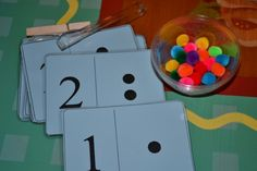 use tweezer or clothespin to put pom-poms on dot cards