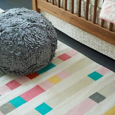 Shop Floral Pouf. This floral pouf features plenty of appliquéd felt flowers and a neutral grey color that helps it fit in any playroom or living room. Plus, you can even use it as an ottoman.