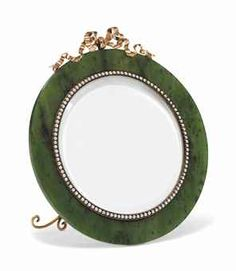 A FABERGÉ JEWELLED GOLD-MOUNTED NEPHRITE PHOTOGRAPH FRAME, WORKMASTER MICHAEL PERCHIN, ST PETERSBURG, 1899-1903. Circular, centring a circular aperture within a seed-pearl border, surmounted by a rose gold ribbon crest.