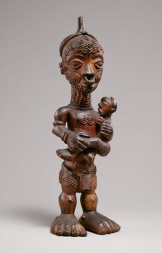 Maternity Figure (Bwanga bwa Cibola)   19th–early 20th century Geography: Democratic Republic of the Congo Culture: Luluwa peoples Medium: Wood, metal ring Dimensions: H. 9 3/4 x W. 3 x D. 2 1/2 in. (24.8 x 7.6 x 6.4 cm)  Procreation is an essential goal in Luluwa society and consequently manga are often called upon to boost fertility and protect pregnant women, newborns, and small children. Manga utilize power objects, or bwanga, as containers and focal points of supernatural forces...