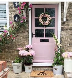 Decorate your front door with lots of seasonal flowers and pots to make it feel like summer. The pastel pink front door is the dream! We're not just your average doormat. Our doormat is produced from the best quality & well coloured doormat base and Front Door Paint Colors, Painted Front Doors, Front Door Decor, Cottage Front Doors, Yellow Houses, Seasonal Flowers, Jolie Photo, Rose Cottage, House Front