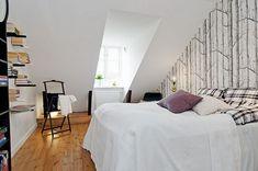 Dormitor in mansarda cu tapet cu copaci