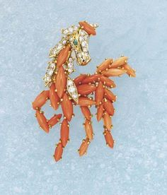 CARTIER A Diamond and Coral Clip, circa 1955  Designed as a horse, the body composed of navette-shaped cabochon coral and a pavé-set diamond head enhanced with an emerald-set eye, mounted in gold, length 4.5 cm.  Signed 'Cartier'