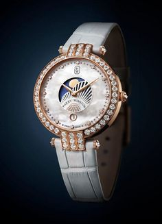 The Harry Winston Premier Moon Phase 36mm features a 36-mm-diameter case made of 18k rose gold with a bezel set with 57 brilliant cut diamonds (approximately 2.32 carats).  This watch is powered by Caliber HW5201 and comes on a white alligator leather strap with iridescent accents.  More @ http://www.watchtime.com/wristwatch-industry-news/watches/showing-at-watchtime-new-york-2016-harry-winston-premier-moon-phase-36mm/ #harrywinston #watchtime #luxurywatch #ladieswatches