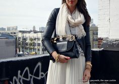 Winter white: White pleated skirt, leather jacket, safety pin clutch