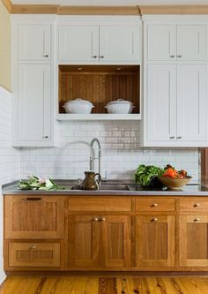Hmm......A classic look for a kitchen. Lots of storage space in beautiful white cabinets, as well as the continuity of the bottom cabinets into the floor makes the space seem larger.