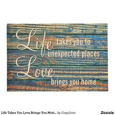 """Life Takes You Love Brings You Motivational Quote. Decorative and trendy design on a stylish and fun door mat. Blue, brown and yellow green colored wooden planks pattern with """"Life takes you to unexpected places, Love brings you home"""" quote. Cute, original and modern home decor product for those looking to decorate their home entrance outside space, or front porch of their beach house, country cottage, log cabin, lake or river vacation home."""