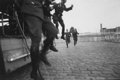 Three West Berlin police officers jump off a truck as two others run to meet them before starting their shifts on guard duty at the Berlin Wall in October 1961