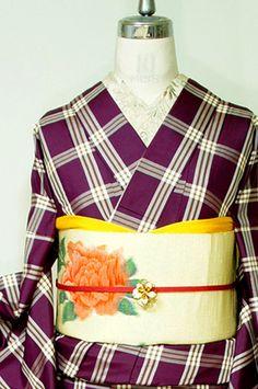 山葡萄のようなこっくりとした赤紫色と清々しい白のバイカラーに、山吹色が挿し色になった色使いも美しく織り出された、大きなチェック模様がモダンな紬の袷着物です。