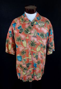 """This vintage Hawaiian shirt was produced by Reyn Spooner for Joe Kealuha. The shirt itself is a reddish orange, and composed of 100% """"Cool Rayon."""" The shirt adorns an atomic style print with a Hawaiian themed motif that features sailboards, pal..."""