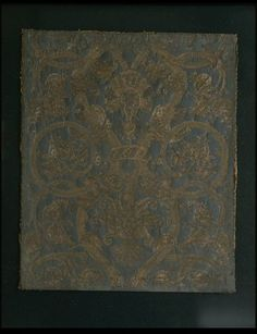 [Italian Leather panel] Gilt leather panel with a pattern of curved and scrolled branches and pomegranates, united by an ornamental ring, and enclosing conventional flowers in gold on a green/blue ground. The gilded parts have been punched with several different stamps. The silverfoil measures 7 x 7 cm (circa). This panel was part of a large hanging. ca 1500-1600 | V Museum, London