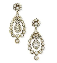 """A pair of 19th century diamond earrings. photo Bonhams. Each stylised flowerhead surmount suspending an openwork pear-shaped pendant with a foliate cluster swing centre, terminating in a single articulated drop, collet-set thoughout with cushion-shaped and old brilliant-cut diamonds, mounted in silver and gold, composite, diamonds approximately 7.50 carats total, length 5.6cm., later post fittings, fitted case by Harvey & Gore, 1 Vigo Street, London."""