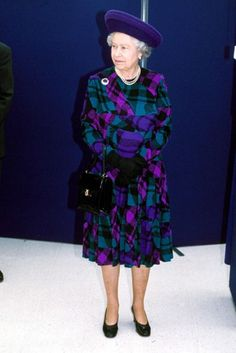 Giving traditional tartan a hint of modern zing, Her Majesty looked colourful in purple and turquoise with an upturned purple hat, at Nottingham University in 1999.