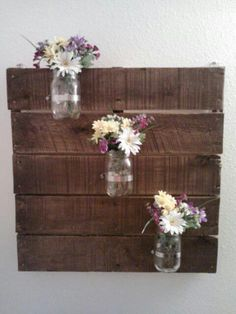 Old pallet turned wall decor for bathroom. Sanded and stained pallet, used pipe clamps to hold the mason jars in place.