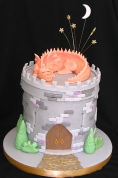 Ice with buttercream. Make white chocolate bricks and a chocolate door.  Put baby dragon on top.  Maybe try green meringue trees around the base.