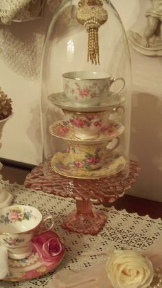If you like vintage, shabby or just plain charming...you should like this! Cloche, pink cake stand, stacked tea cups and a tassel on top!