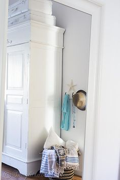 Bedroom decor. Ikea Hemnes mirror in bedroom with painted suitcases, white painted wardrobe and a pretty board with hooks via songbirdblog.com