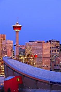 Picture of the Saddledome standing before the Calgary Tower as the City of Calgary skyline glows at sunrise.