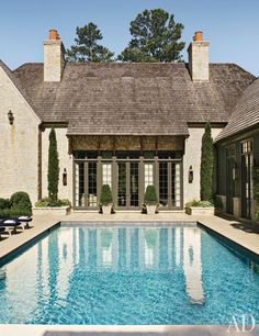 French doors offer free flow between the indoors and the pool terrace at an Atlanta home by architect William T. Baker.