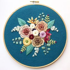 An 8 original hand embroidered art piece. This hoop features a jewel and earth toned bouquet on a rich blue background, and is stretched and hand stitched upon cotton flannel in a 8 hoop, which serves as its ready-to-hang frame. The back of each hoop is glued with felt, and a sweet