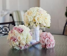 Simple, elegant bouquets of white, cream and light pink flowers are wrapped in satin ribbons.