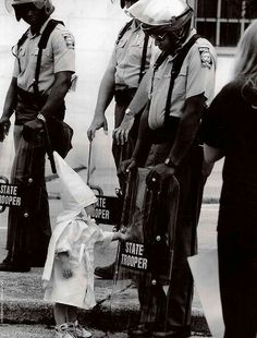 The child of a KKK member approaches a black state trooper in 1992. This proves racism is a learned trained emotion.