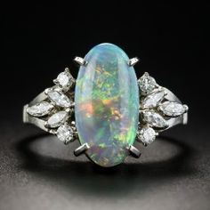 A psychedelic array of electric rainbow colors radiate from this fabulous elongated oval Australian black opal, weighing 1.86 carats and measuring just over a half-inch long. Hand fabricated in platinum, this mesmerizing estate jewel is embellished on each side with sparkling sprays composed of marquise and round brilliant-cut diamonds and is finished all around the gallery with fanciful open scroll work. Size 5.