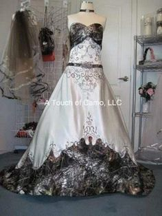 Anita is a strapless ball gown with cathedral train in white or ivory with camouflage accents. Shown in mossy oak camo and white satin.  I know my gown will not be camouflage but if it was this is it!