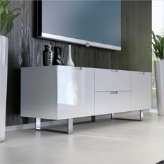 "Modloft Eldridge 59"" Entertainment Unit in White Lacquer - The Eldridge Entertainment Unit/ TV stand in White Lacquer has contemporary flair and conventional use to be more then a pretty piece in your living room. This TV console has solid hardwood construction for durability while two drawers and two cabinets supply ample storage options. The Eldridge Entertainment Unit is the perfect functional, stylish addition for your cutting-edge minimal decor."