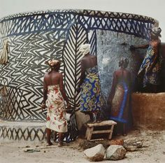 Women painting a traditional mud house with zigzag notifs – Kassena Compound, Ghana