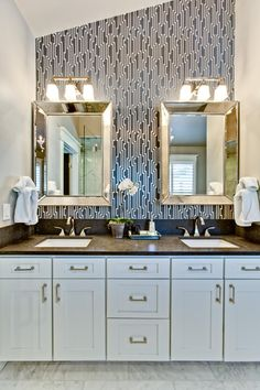 Graphic black-and-white wallpaper brings a contemporary vibe to this sleek bathroom. White cabinets contrast against the dark brown countertops of the double vanity, which features elegant gold hardware. A pair of beveled mirrors help to bounce light around the space and enlarge the room.