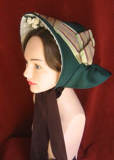Basic spoon bonnet - the buckrim form is covered in a smooth silk and trimmed with a wide stripe ribbon. The full curtain set in the back serves both as a fashion detail and a protection from the sun.
