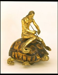 Mechanical tortoise with triton winder, 1600-1650. In this example the tortoise's head jerks in and out from under its shell as the object is rolled along. The merman on top of the shell (known as a triton) is designed to raise its arms and bring its trident down on the head of the moving tortoise.