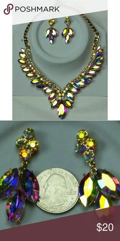 """Gorgeous Rhinestone Necklace & Earring Set This set is absolutely fantastic! Multi-faceted rhinestones that change colors, depending on the light. Color can change from pink, purple, green & blue, among others. On an adjustable gold-toned chain w/ a lobster claw clasp. Deep V center measures approx 5"""" from where it attaches to the chain. There are some minor scratches on some of the rhinestones but they don't take away from it's brilliance. Comes w/ matching earrings. Adjustable from 20""""…"""